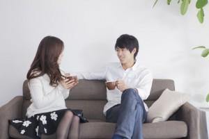 ソファーで座って会話をする男性と女性